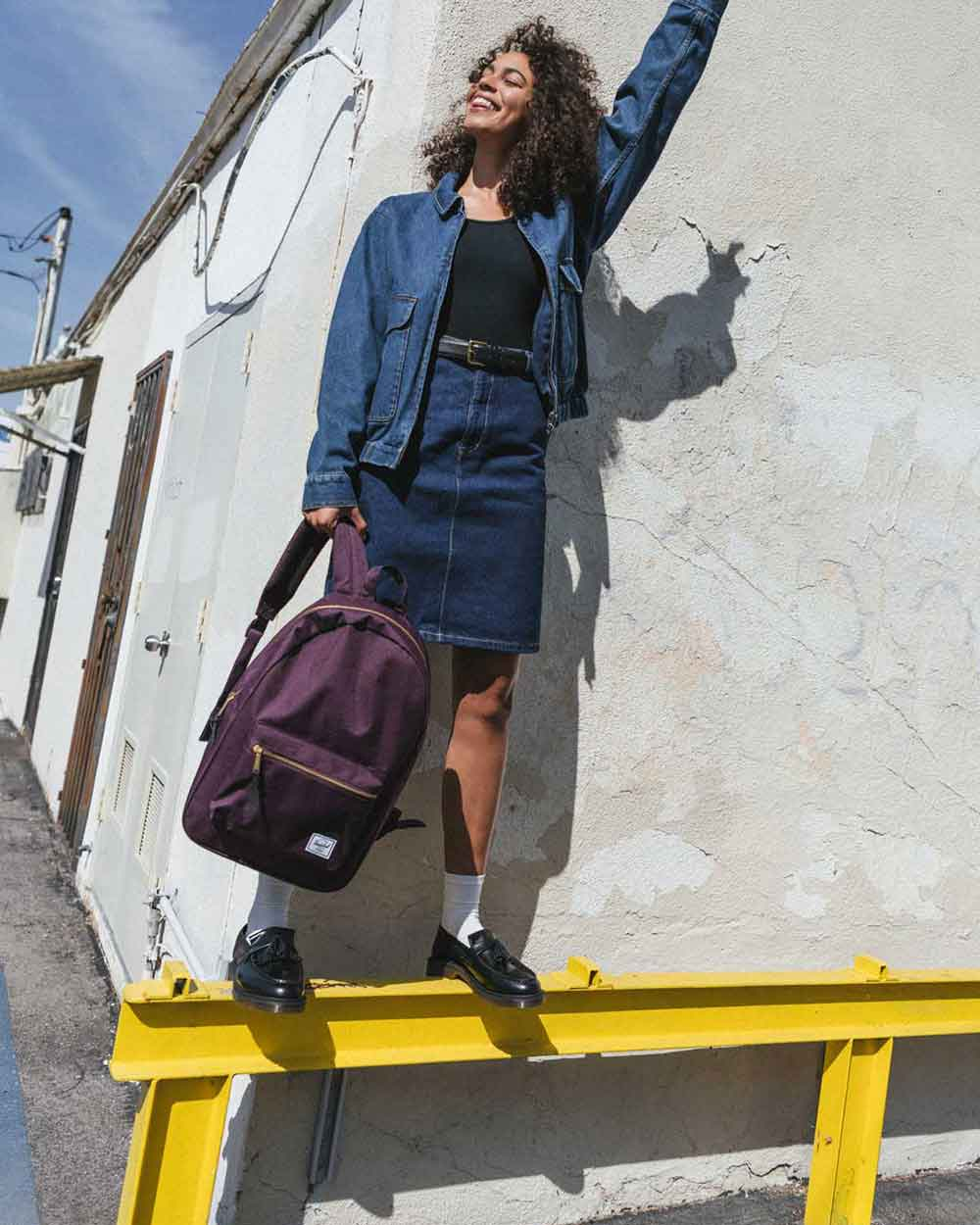 A woman standing on a railing holding a Blackberry Wine Nova Backpack Mid-Volume